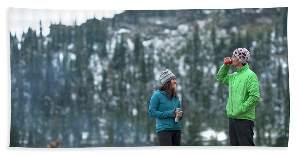 Tree Bath Sheet featuring the photograph Couple Standing By A Campfire by Woods Wheatcroft