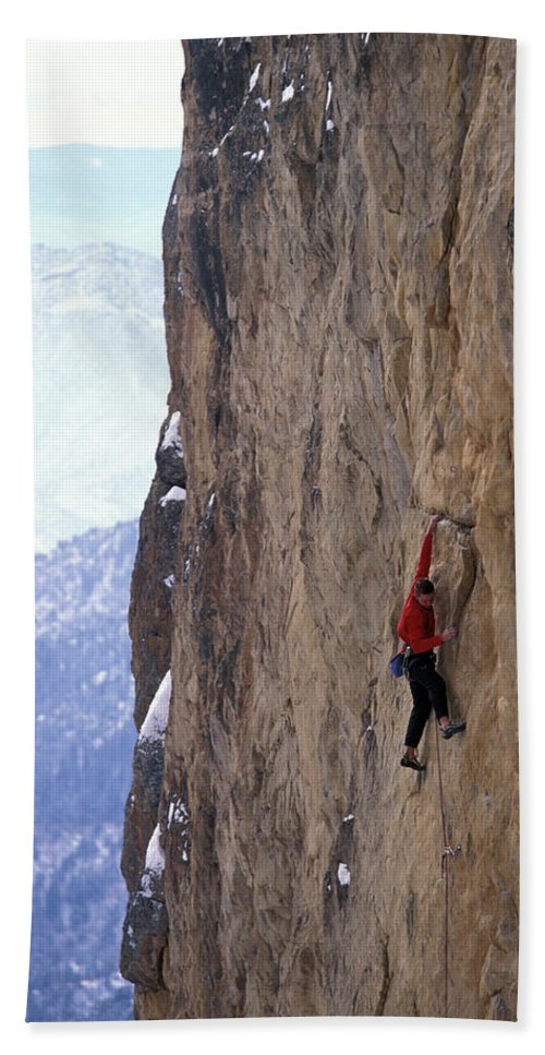 Action Bath Towel featuring the photograph Man In A Red Shirt Lead Climbing by Corey Rich