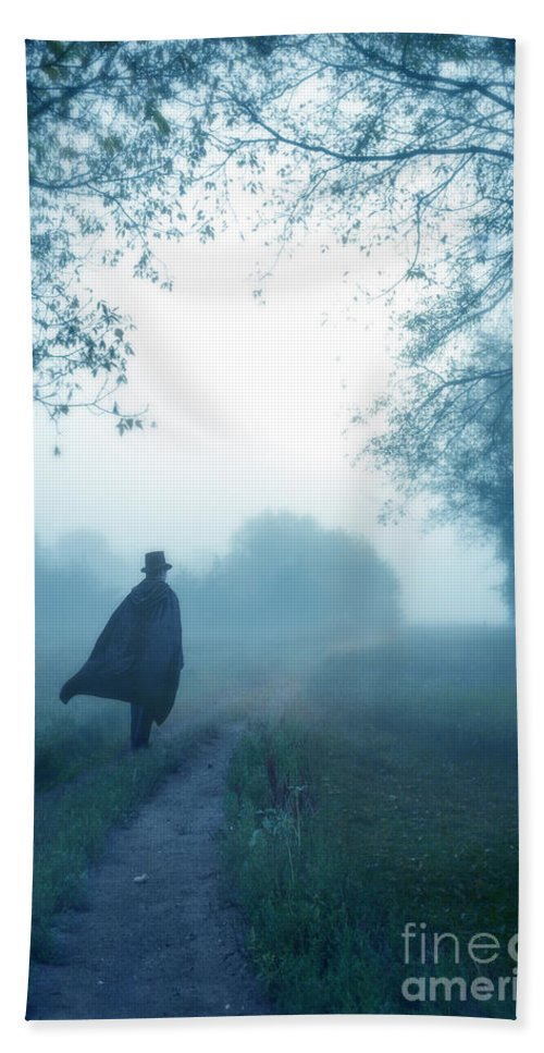 Man Hand Towel featuring the photograph Man In Top Hat And Cape On Foggy Dirt Road by Jill Battaglia