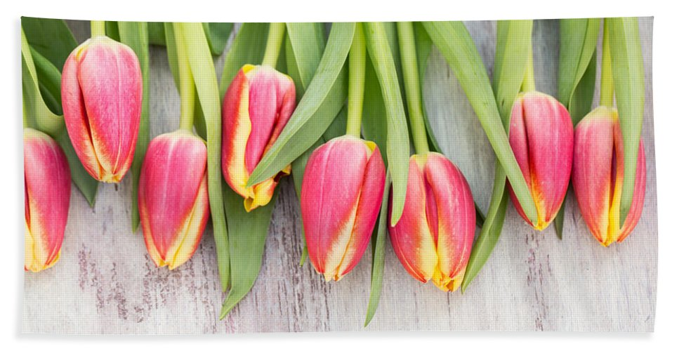 Easter Bath Sheet featuring the photograph Many Spring Tulip Flowers On White Wood Table by Carol Mellema