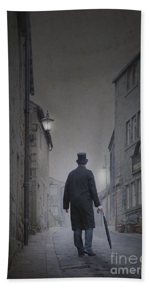 Man Bath Sheet featuring the photograph Victorian Man In Top Hat On A Cobbled Road At Night by Lee Avison