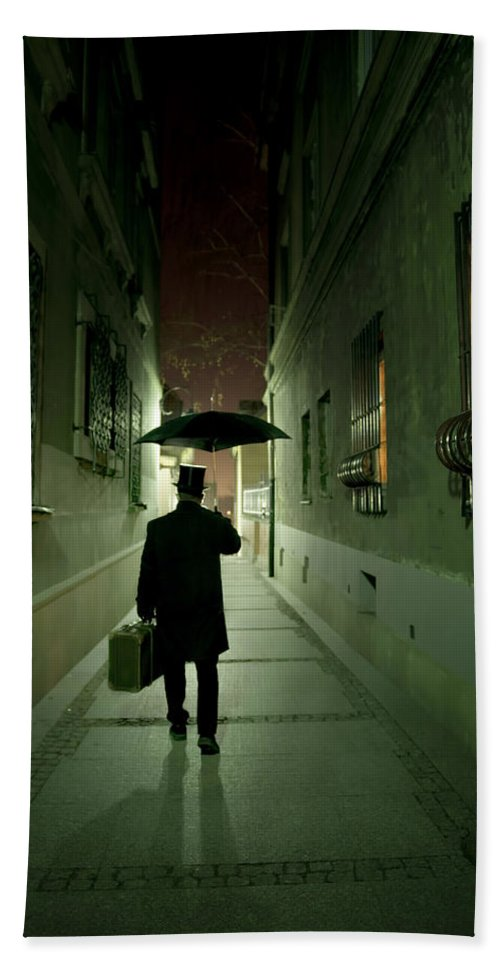 1800 S Hand Towel featuring the photograph Victorian Man With Top Hat Carrying A Suitcase And Umbrella Walking In The Narrow Street At Night by Jaroslaw Blaminsky