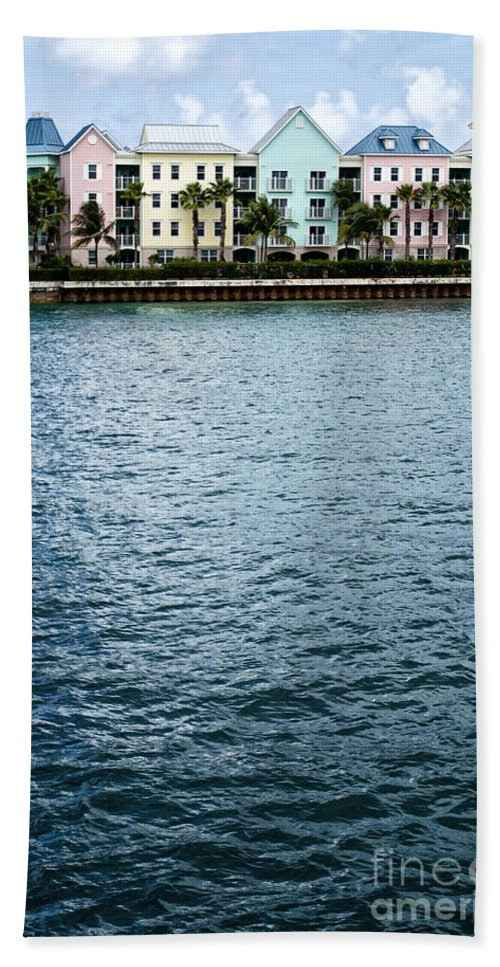 House; Condo; Townhome; Water; Shallow; Island; Tropical; Shore; Waterfront; Bahamas; Blue; Sky; Clouds; Trees; Buildings; Colors; Colorful; Pink; Yellow; Green; Festive; Palm Trees; Outside; Outdoors; Exterior; Home; Tropics; Row Hand Towel featuring the photograph Waterfront Colors by Margie Hurwich