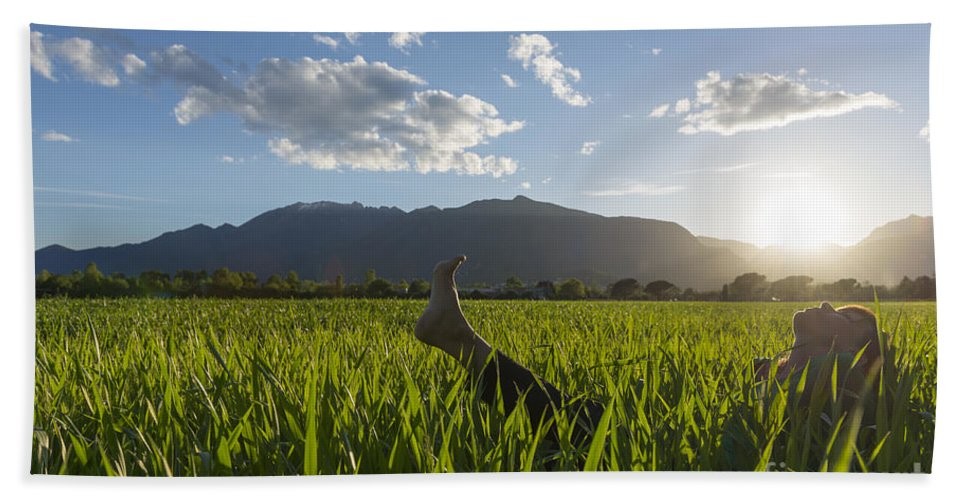 Woman Bath Sheet featuring the photograph Woman Lying Down On A Green Field by Mats Silvan