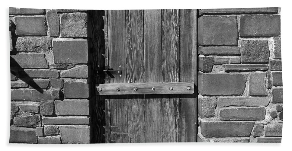 Black And White Bath Sheet featuring the photograph Wooden Door And Stone Wall 1 by Denise Mazzocco