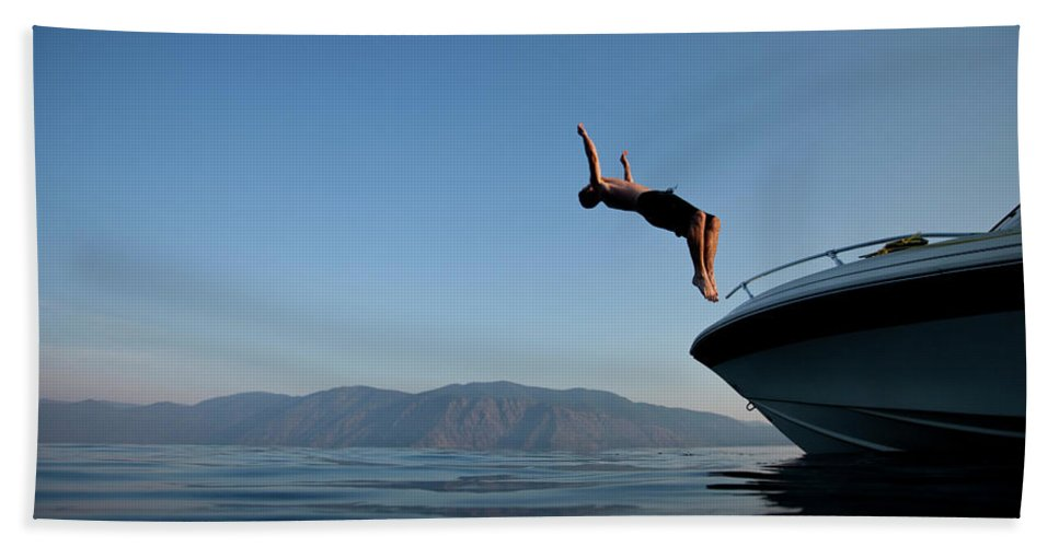 Adult Bath Sheet featuring the photograph Young Man Flips Off A Boat At Sunset by Patrick Orton