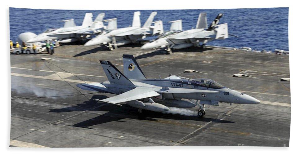 Uss Dwight D Eisenhower Hand Towel featuring the photograph An Fa-18e Super Hornet Lands Aboard by Stocktrek Images
