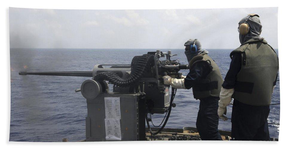 Submarine Tender Hand Towel featuring the photograph Gunner Fires A Mark 38 Machine Gun by Stocktrek Images