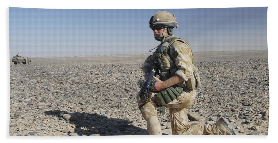 Foreign Military Bath Sheet featuring the photograph A British Army Soldier On A Foot Patrol by Andrew Chittock