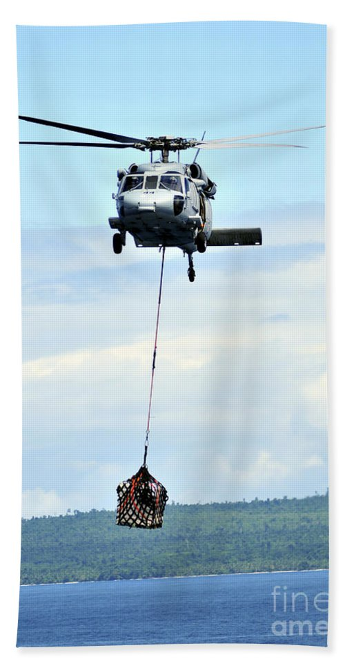 Mh-60 Hand Towel featuring the photograph A Mh-60 Knighthawk Carries Supplies by Stocktrek Images