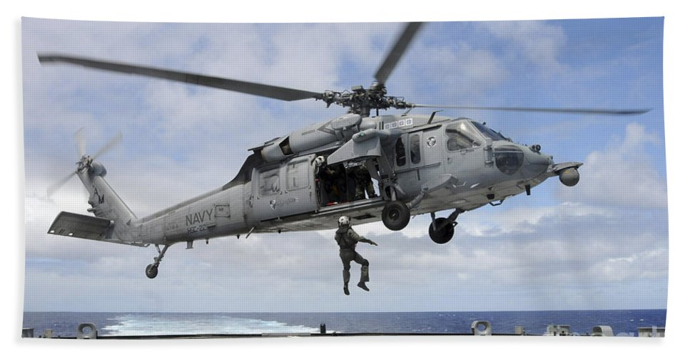Rimpac Hand Towel featuring the photograph A Naval Aircrewman Is Hoisted Into An by Stocktrek Images
