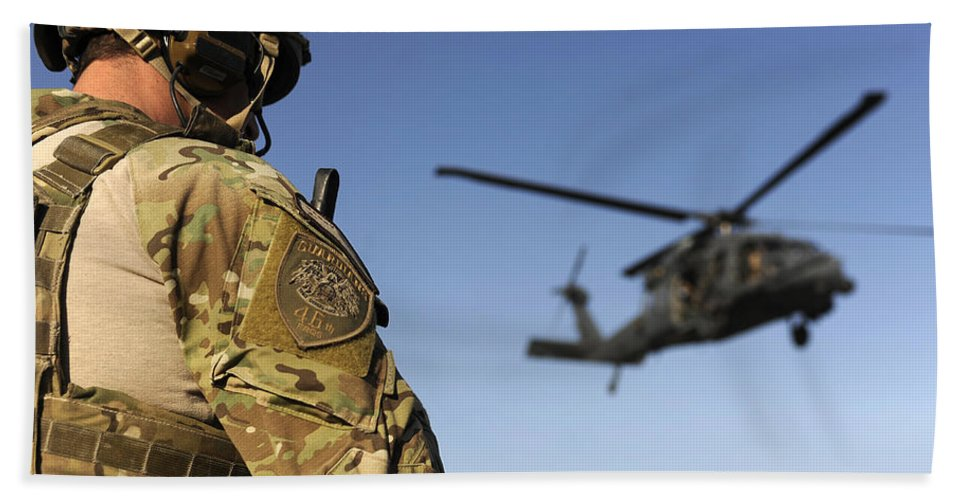 Afghanistan Hand Towel featuring the photograph A Pararescueman Awaits The Landing by Stocktrek Images