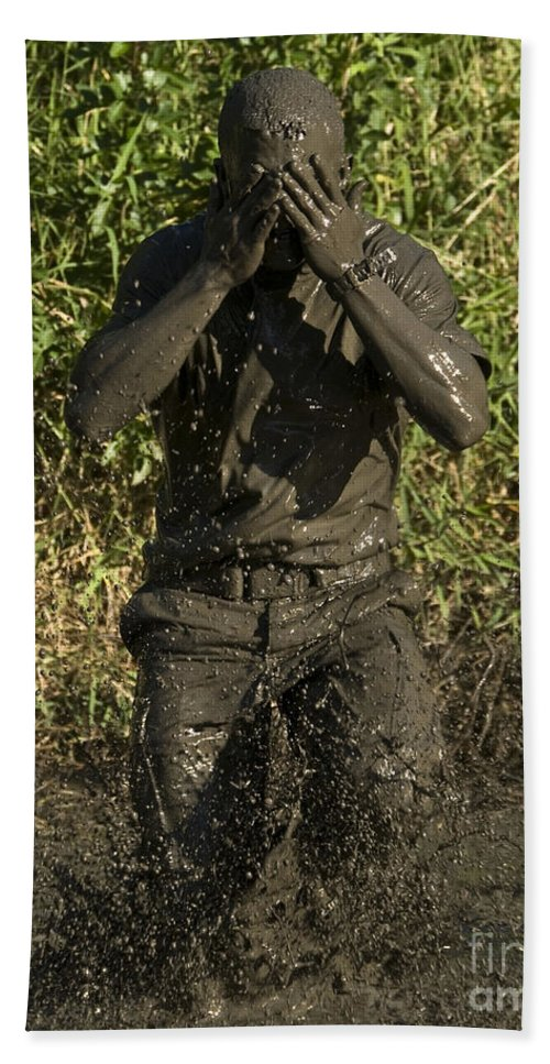 Physical Training Hand Towel featuring the photograph A Participant Wipes Mud From His Face by Stocktrek Images