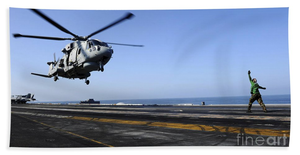 Uss John C Stennis Hand Towel featuring the photograph Airman Directs An Eh-101 Merlin by Stocktrek Images