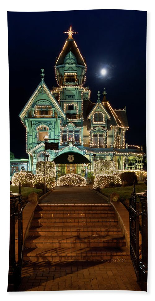 Carson Mansion Bath Sheet featuring the photograph Carson Mansion At Christmas With Moon by Greg Nyquist