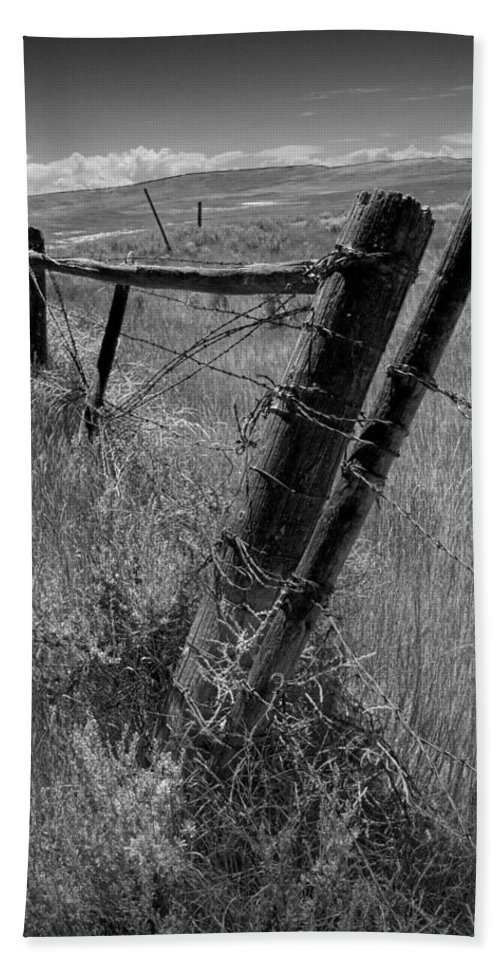 Art Bath Sheet featuring the photograph Fence Posts And Barbed Wire At The Edge Of A Field In Montana by Randall Nyhof