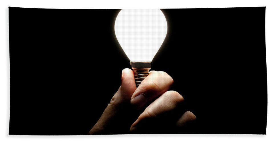 Light Bulb Hand Towel featuring the photograph Lit Lightbulb Held In Hand by Simon Bratt Photography LRPS