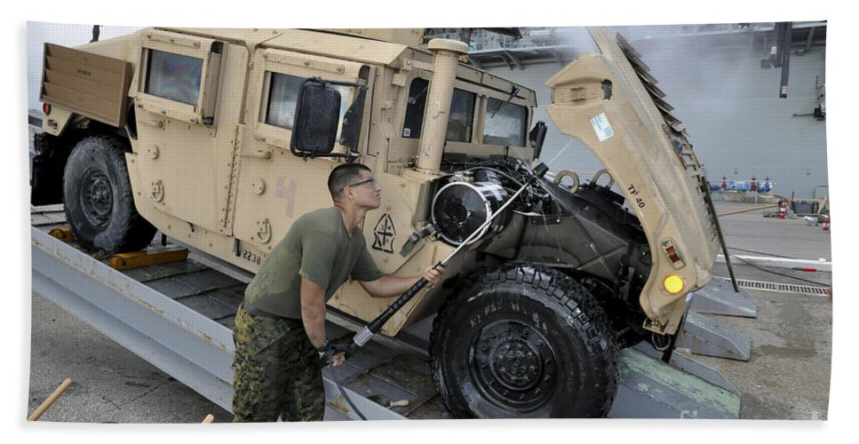 Maritime Hand Towel featuring the photograph Marine Uses A Pressure Washer To Clean by Stocktrek Images