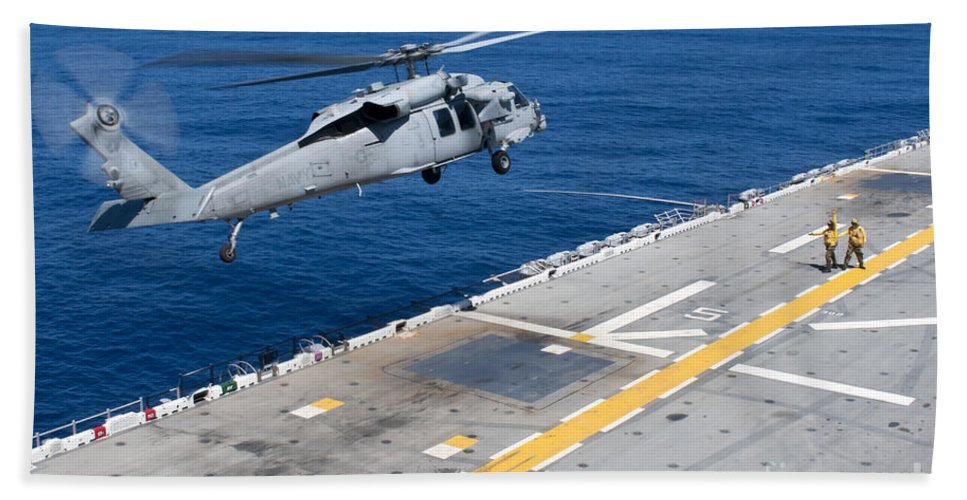 Us Navy Hand Towel featuring the photograph N Mh-60s Sea Hawk Helicopter Lifts by Stocktrek Images