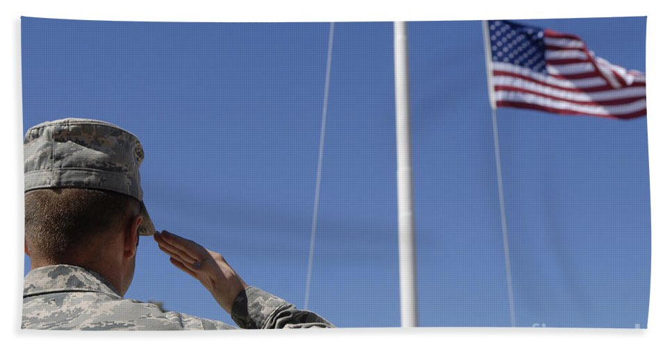 Soldier Hand Towel featuring the photograph A Soldier Salutes The American Flag by Stocktrek Images