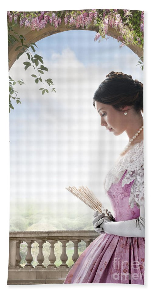 Victorian Hand Towel featuring the photograph Beautiful Victorian Woman In Pink Dress Standing Under A Wisteri by Lee Avison