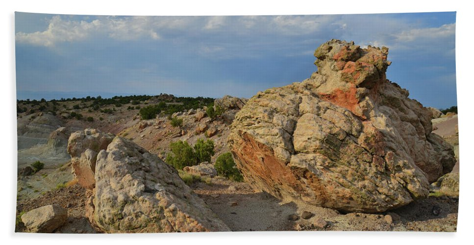Little Park Road Bentonite Site Bath Sheet featuring the photograph Evening Light On Boulders Of Bentonite Site by Ray Mathis