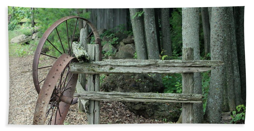 Wagon Wheel Bath Sheet featuring the photograph Old Rusty Wagon Wheels And Weathered Fence by Anita Hiltz