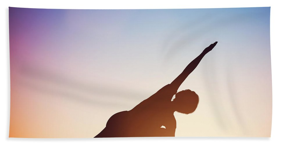 Yoga Bath Sheet featuring the photograph Woman Standing In Revolved Side Angle Yoga Pose Meditating At Sunset by Michal Bednarek