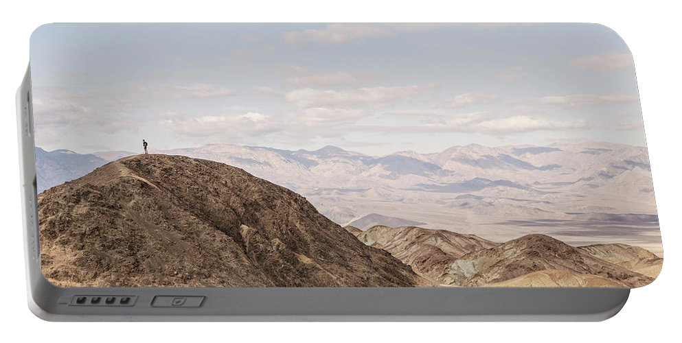 Arid Portable Battery Charger featuring the photograph A Hiker Stands On A Peak by Chris Bennett