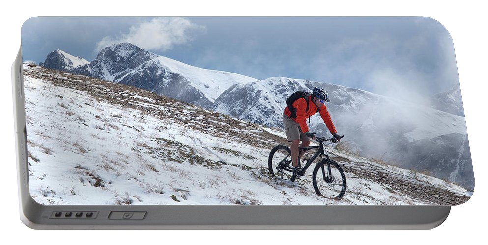 35-39 Years Portable Battery Charger featuring the photograph A Mountain Biker Rides Through The Snow by Menno Boermans