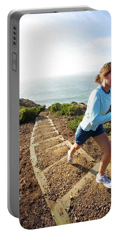 California Portable Battery Charger featuring the photograph A Woman Running Stairs Near The Ocean by Corey Rich