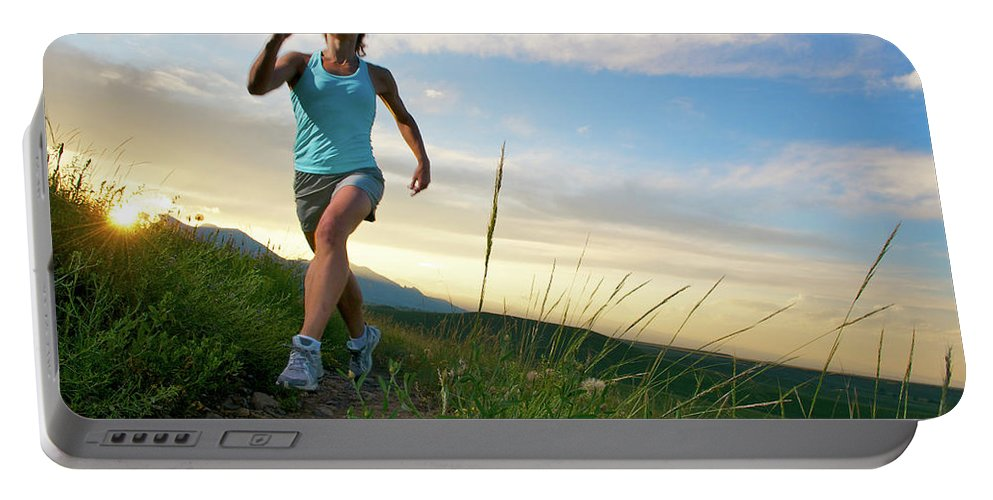 20s Portable Battery Charger featuring the photograph A Woman Trail Running Near Boulder, Co by Celin Serbo