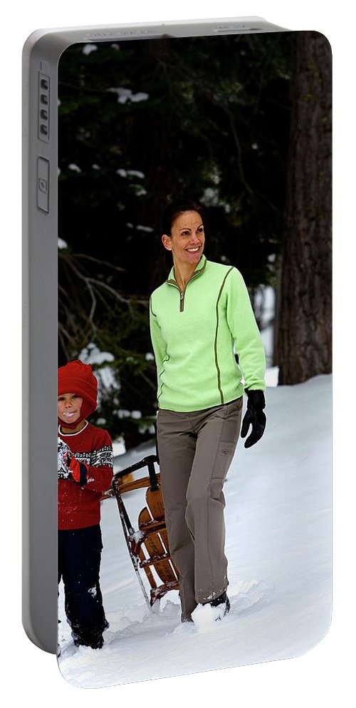 Action Portable Battery Charger featuring the photograph A Young Boy And Mother Sledding by Corey Rich