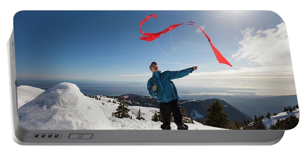 Full Length Portable Battery Charger featuring the photograph Flying A Kite On A Snowy Mountain by Christopher Kimmel