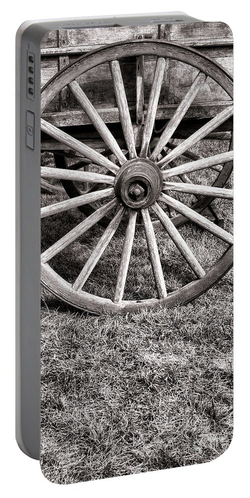 Schooner Portable Battery Charger featuring the photograph Old Wagon Wheel On Cart by Olivier Le Queinec