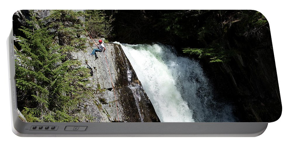 20-24 Years Portable Battery Charger featuring the photograph A Young Man Rappels Down A Cliff Next by Patrick Orton