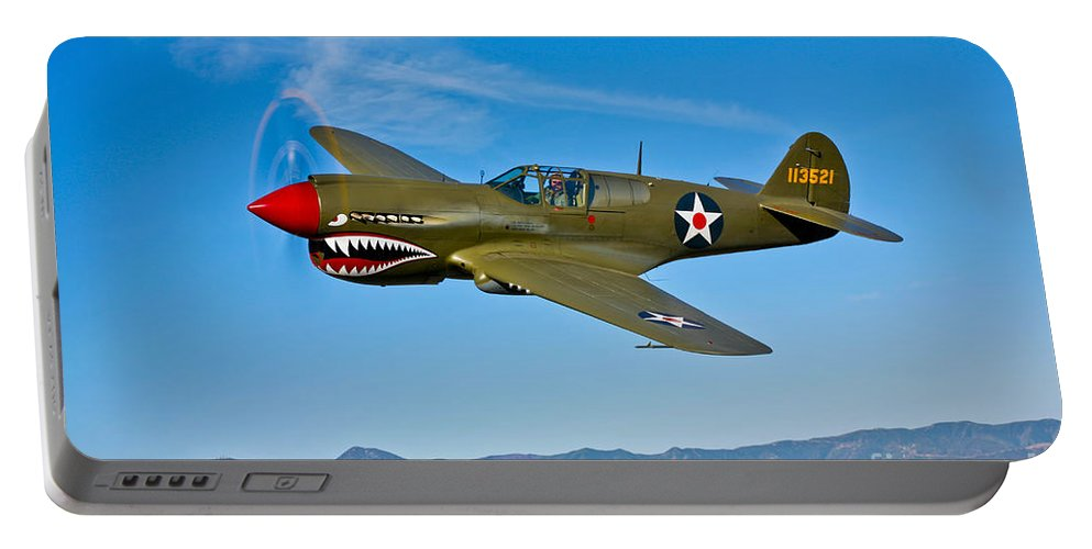 Horizontal Portable Battery Charger featuring the photograph A Curtiss P-40e Warhawk In Flight by Scott Germain
