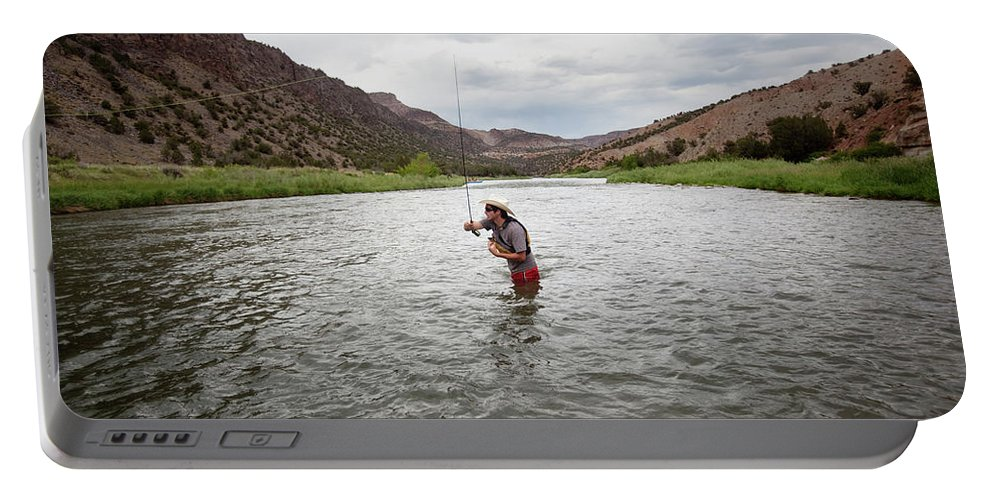 30-34 Years Portable Battery Charger featuring the photograph A Fly Fisherman Mends While Fishing by Ryan Heffernan