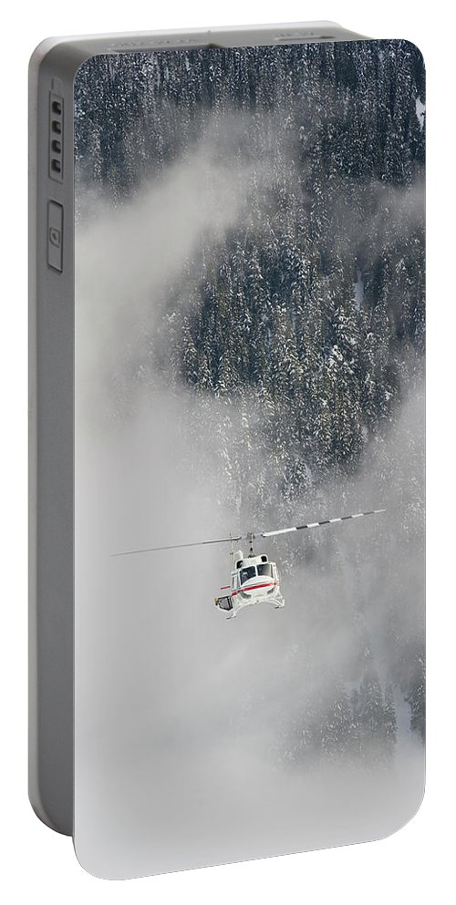 British Columbia Portable Battery Charger featuring the photograph A Heli-ski Helicopter Flies by Topher Donahue