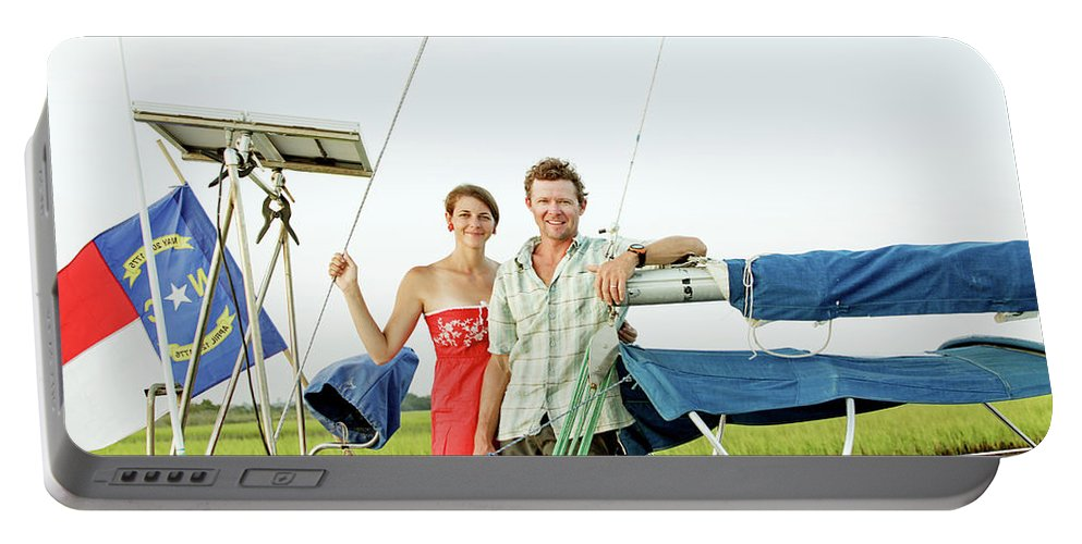 25-29 Years Portable Battery Charger featuring the photograph A Man And A Woman Embrace In Sailboat by Eyeconic Images