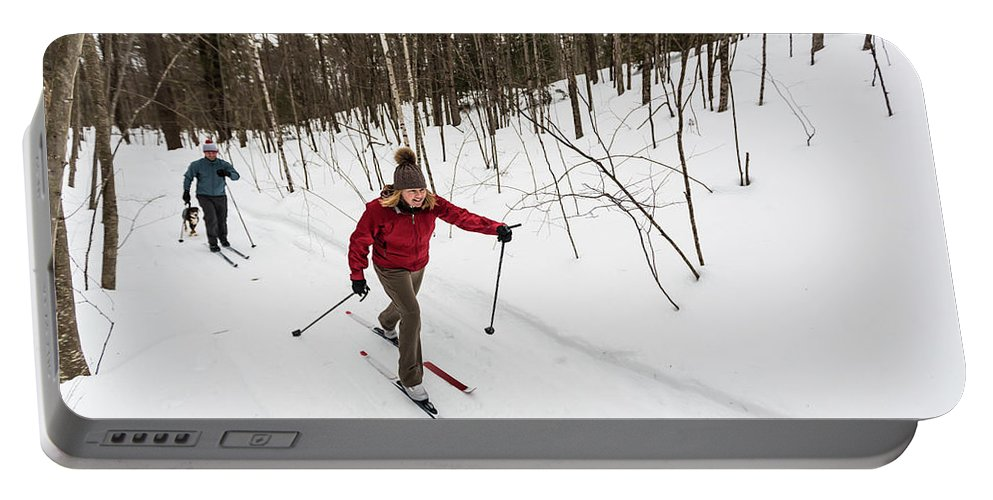 On The Move Portable Battery Charger featuring the photograph A Man And Woman Cross Country Skiing by Jerry Monkman