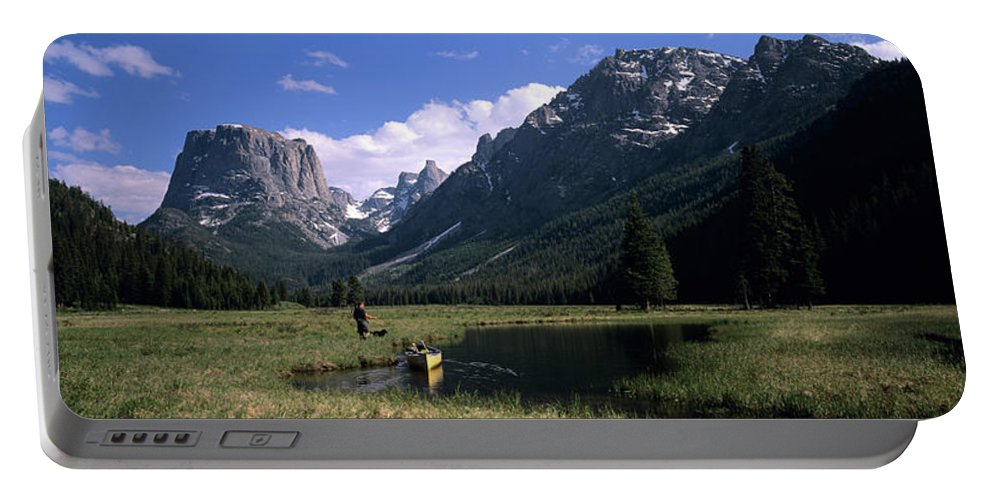 Backcountry Portable Battery Charger featuring the photograph A Man Pulls His Canoe Up A River Valley by David Stubbs