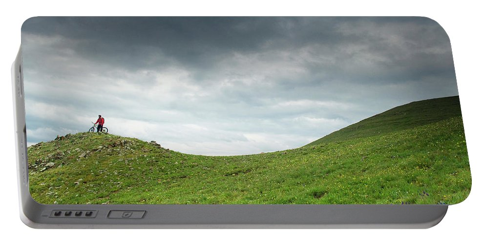 Bicycle Portable Battery Charger featuring the photograph A Man Sitting On Top Of A Tundra Ridge by Keith Ladzinski