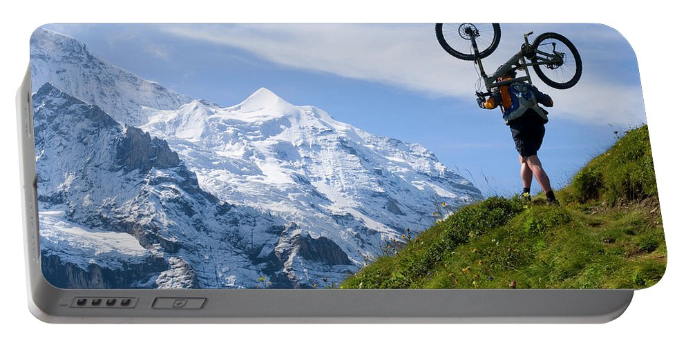 Adult Portable Battery Charger featuring the photograph A Mountain Biker Is Carrying His Bike by Menno Boermans