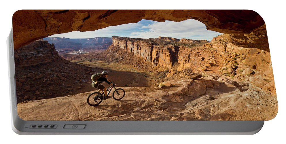 Activity Portable Battery Charger featuring the photograph A Mountain Biker Rides By On Slickrock by Whit Richardson