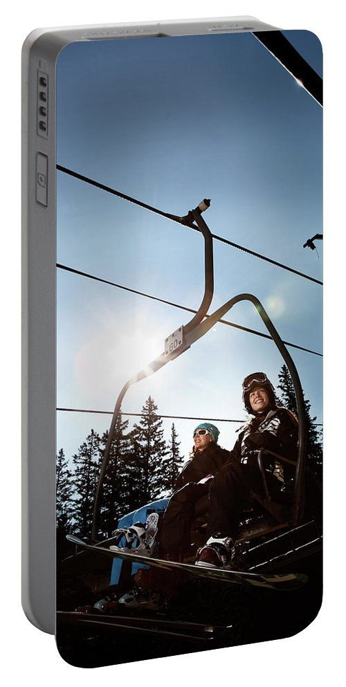 20s Portable Battery Charger featuring the photograph A Skier And Snowboarder Share The Chair by Ryan Heffernan