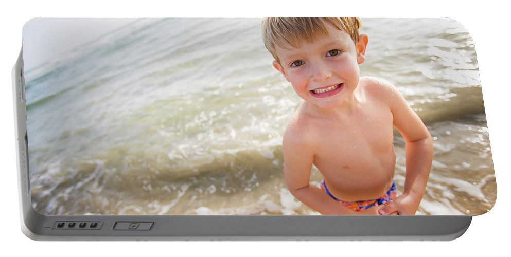 Active Lifestyle Portable Battery Charger featuring the photograph A Smiling Young Boy Enjoys A Sunny by Ty Milford