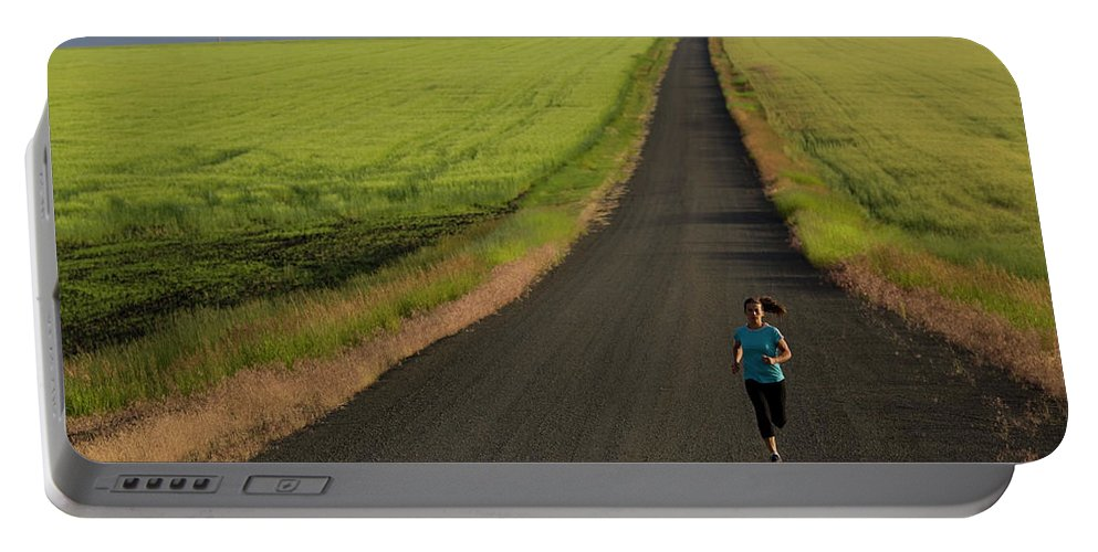 40-44 Years Portable Battery Charger featuring the photograph A Woman Running On A Dirt Road by Woods Wheatcroft