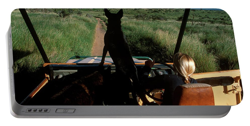 Color Image Portable Battery Charger featuring the photograph A Woman Sits In Her Safari Jeep by David McLain