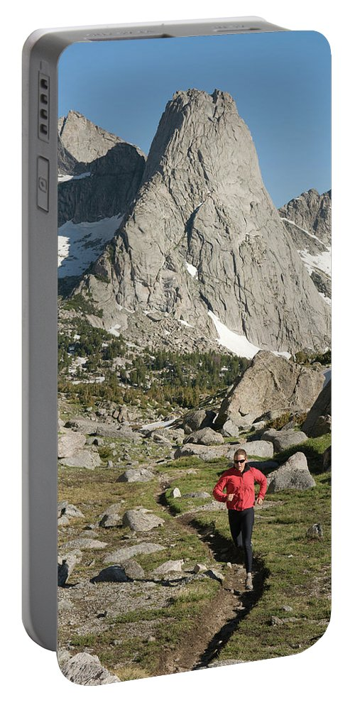 40-44 Years Portable Battery Charger featuring the photograph A Woman Trail Running In The Cirque by Kennan Harvey